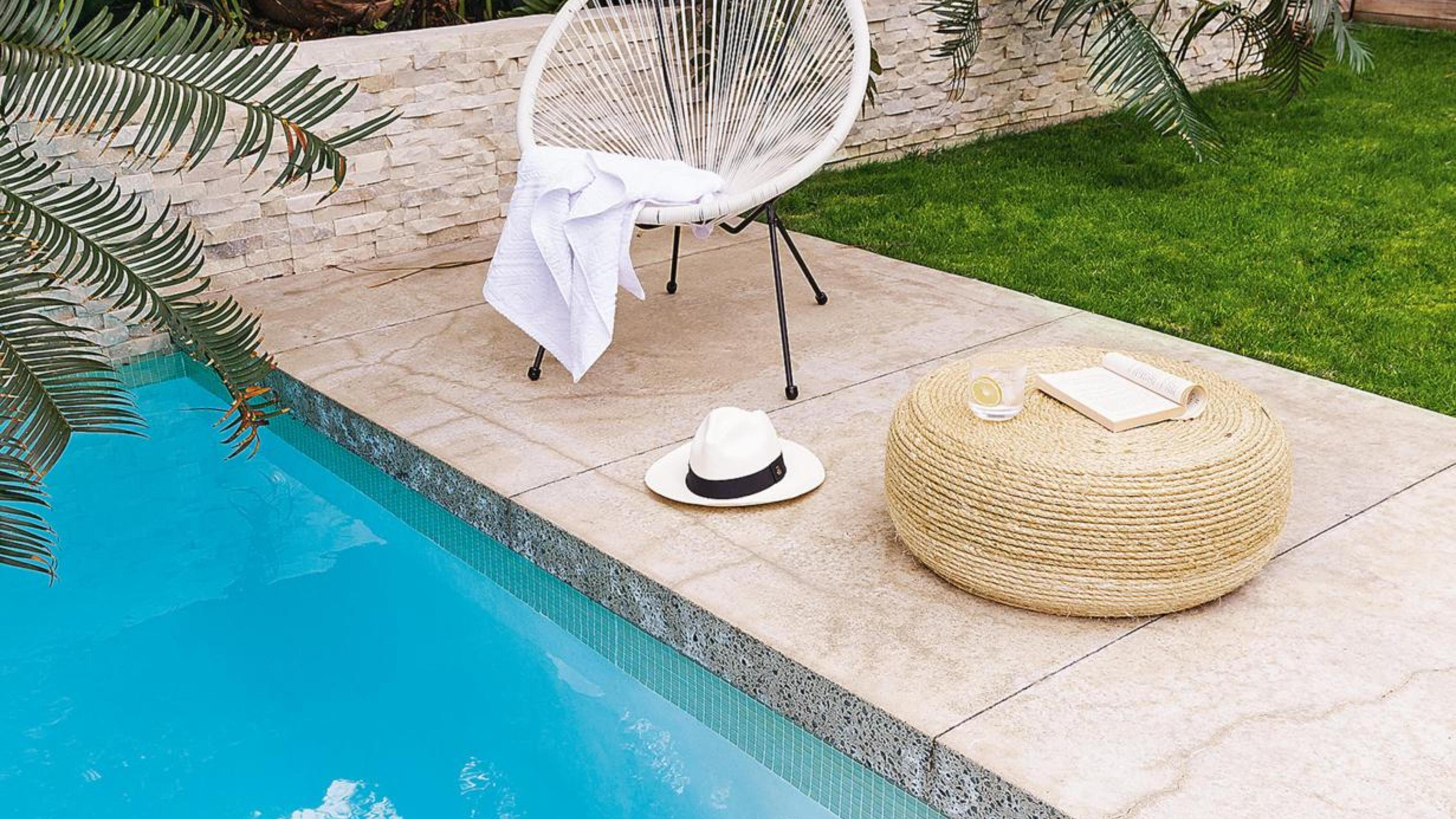 Chair and towel next to pool.