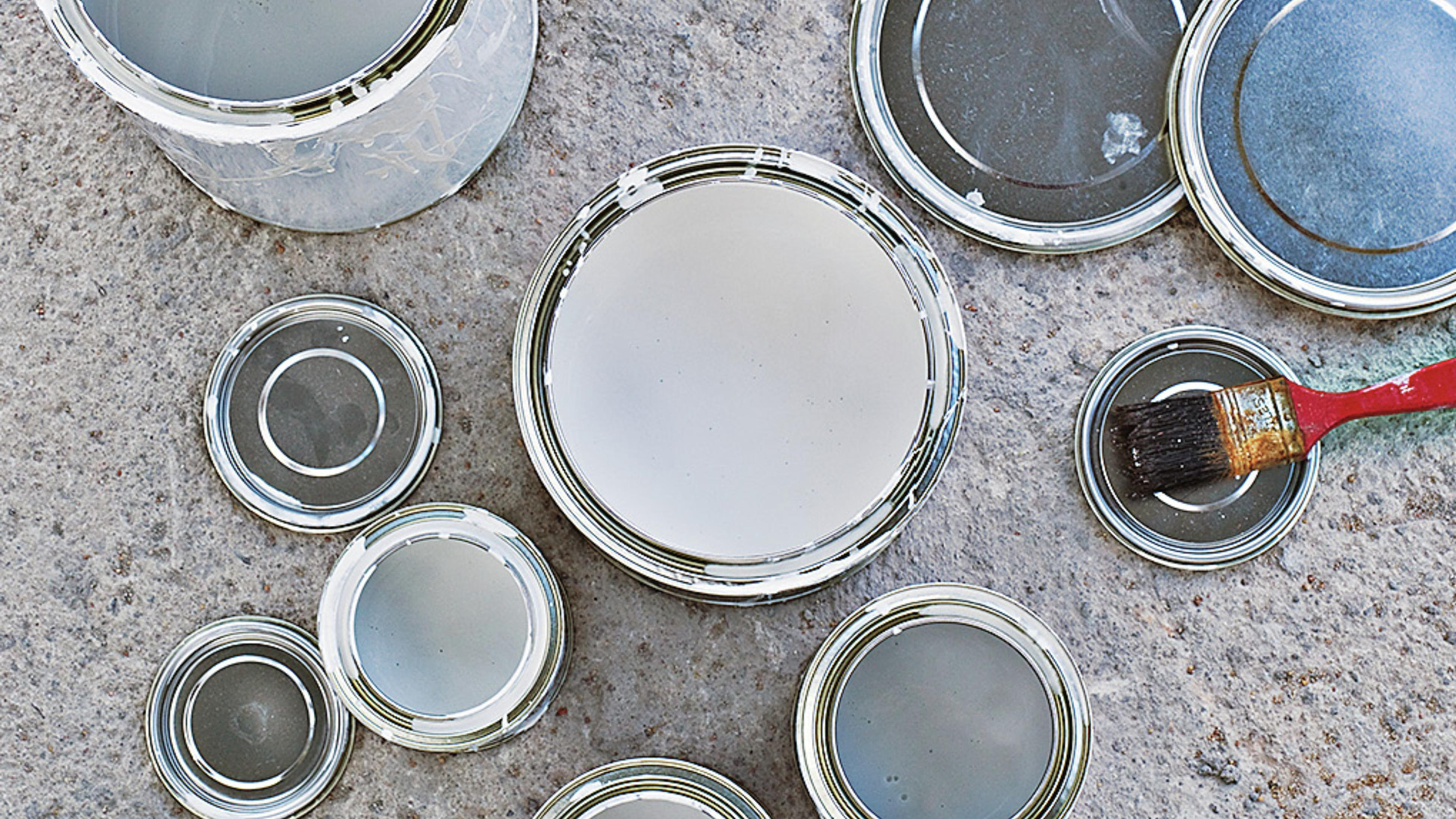 Empty paint tins and lids on the ground.