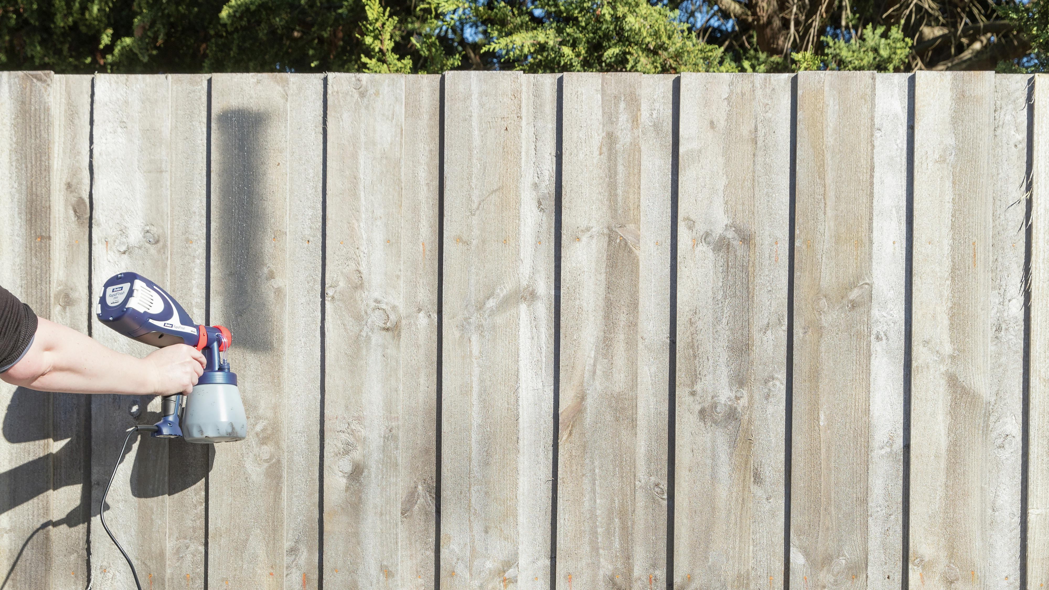 Person spray painting a wooden fence.