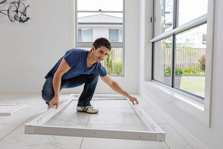 A tradesman about to affix a frame into a windowsill