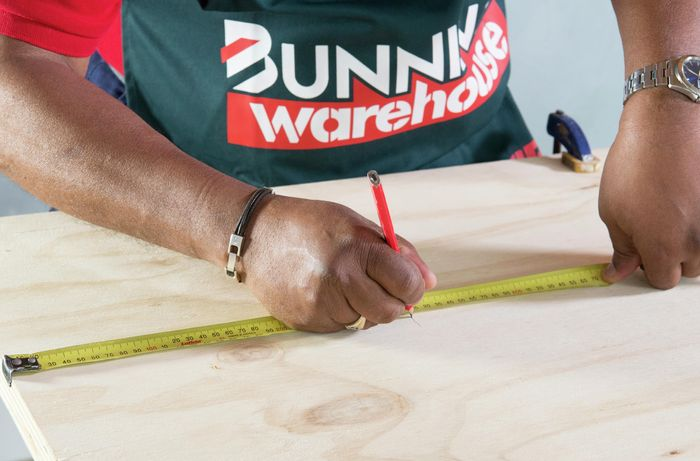 Person marking anchor point on timber with tape measure and pencil