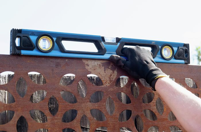 A person holding a spirit level on the top of a steel screen