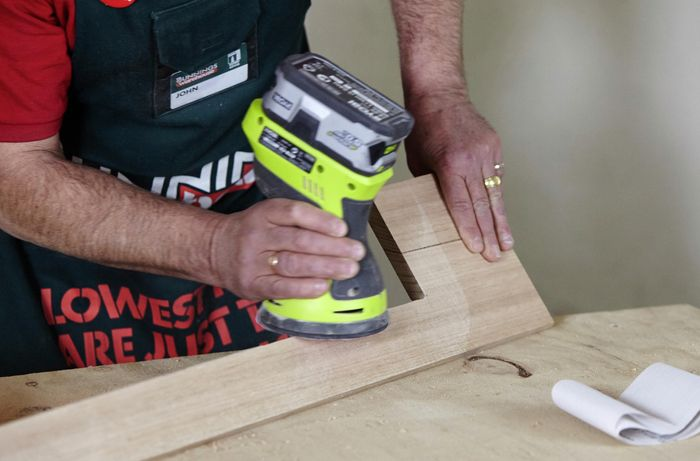 A cordless sander being used to work a piece of timber