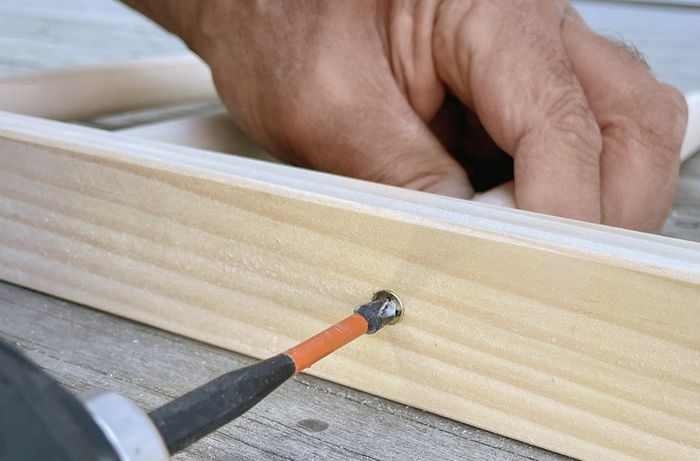 Close up of a pair of hands securing dowel into pine with a screw