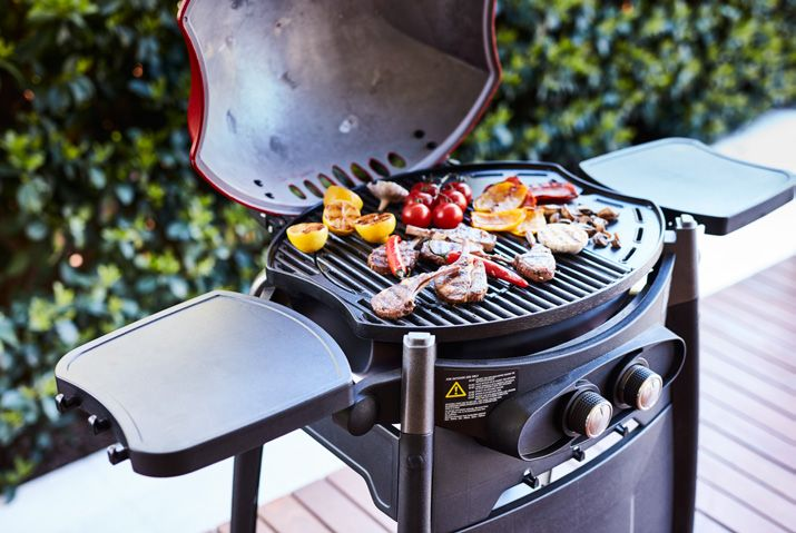 A Gasmate barbecue grilling a variety of meats and vegetables