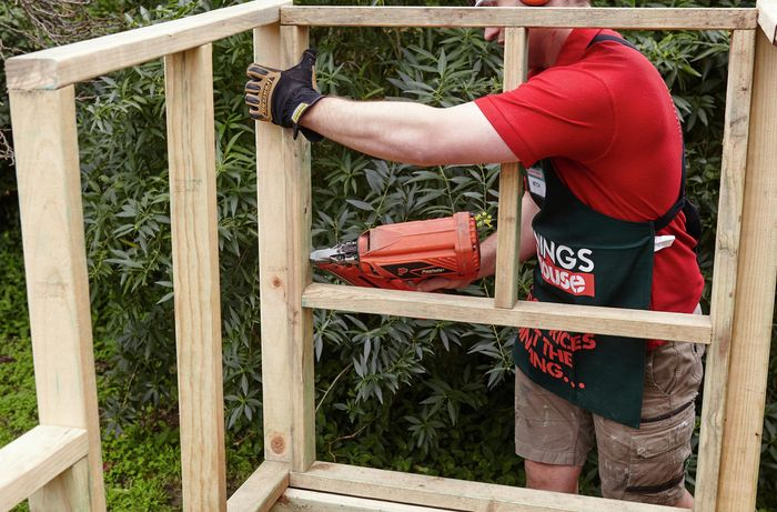 The back of the nesting box being attached to the rest of the chicken coop's wooden framework