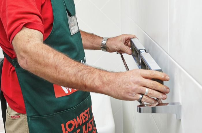 A person checking a towel rail with a spirit level