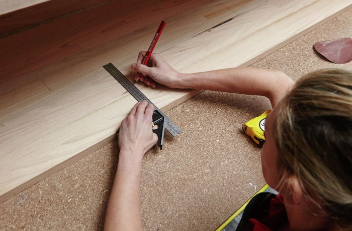 A person marking a measurement onto a timber panel using a set square