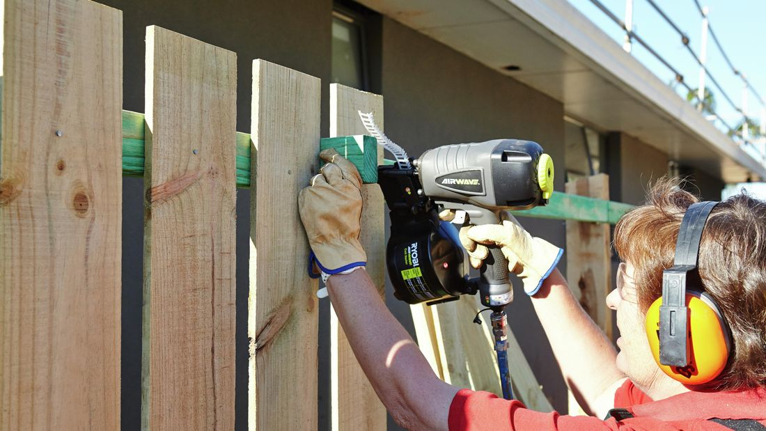 A Bunnings team member nailing a paling to a fence with a nail gun, using a scrap of timber as a spacer between prior palings