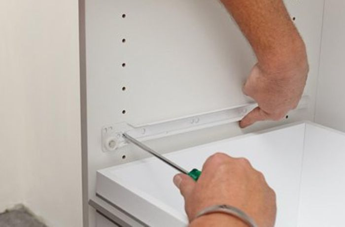 Screwing the drawer runners inside the cabinet.