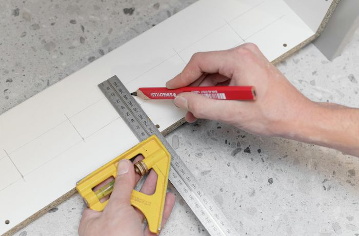 Using pencil and ruler to mark a cabinet.