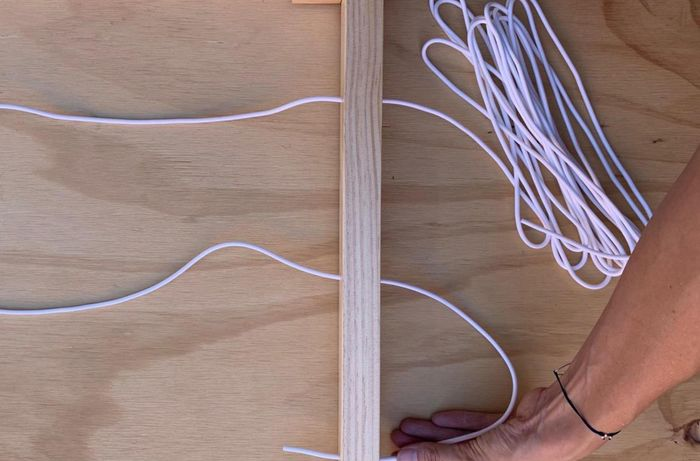 Cord being threaded through holes in a drying rack