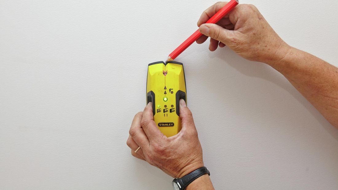Using a stud finder to find and mark the wall studs.