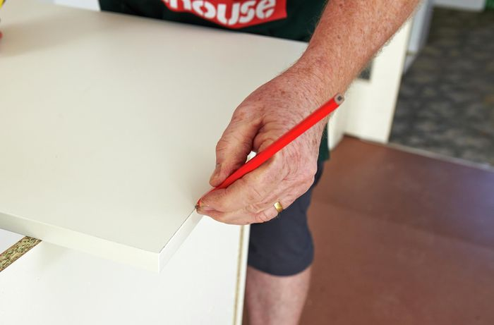 Person marking length of cabinet