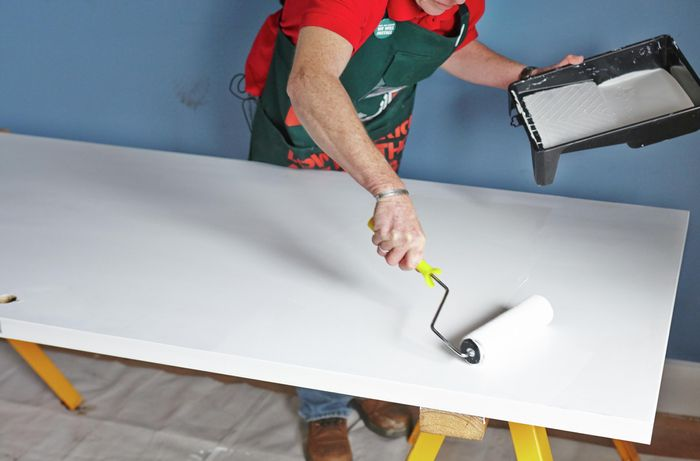 Person painting door with paint roller.