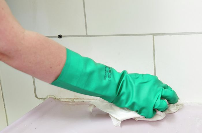 A person wearing rubber gloves wiping a long a line of grout with a rag