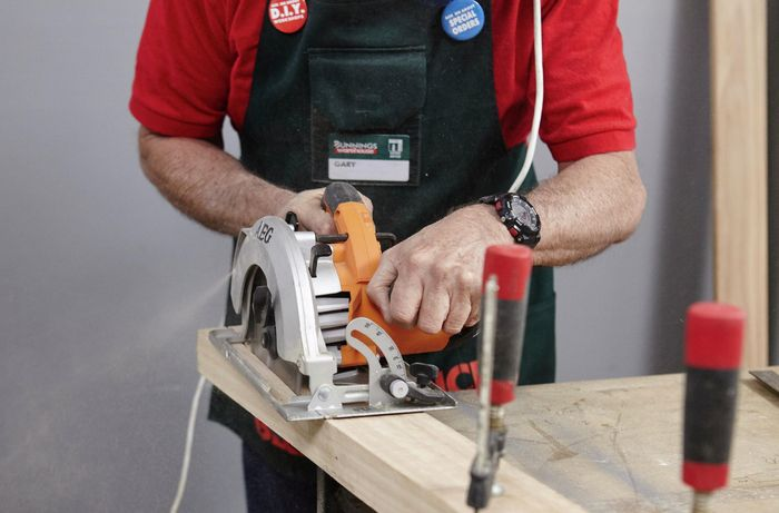 A chair leg being cut along a taper with a circular saw by a Bunnings team member