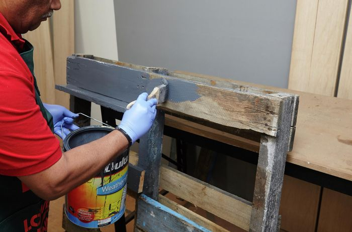 A person painting a shelving unit made of recycled timber