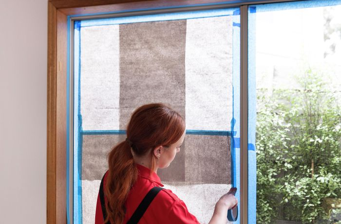 paper and painter's tape being used to protect a window from spray paint