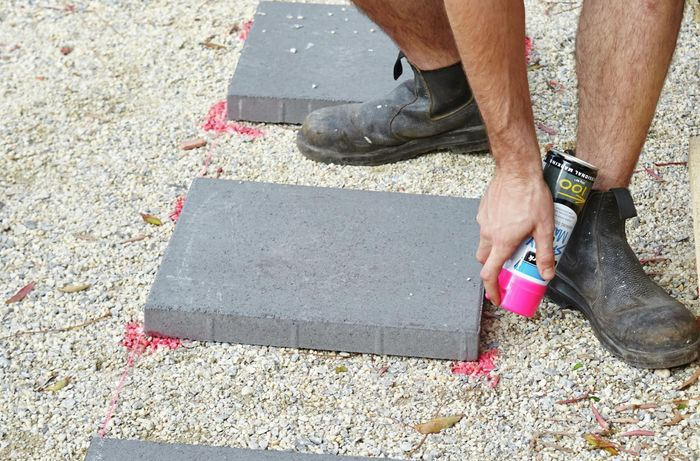 A person marking the ground with spray paint at the corner of a paver