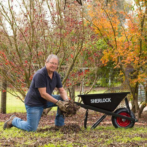 Man putting leaves into a black Sherlock wheelbarrow