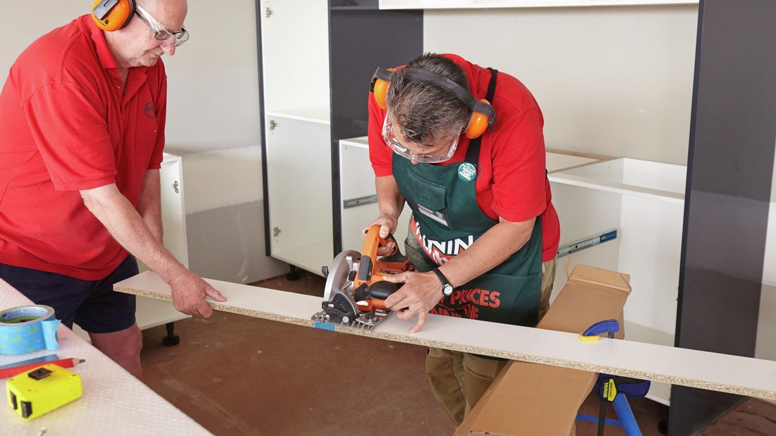 One person cutting a length of kickboard with a circular saw while another person holds the end