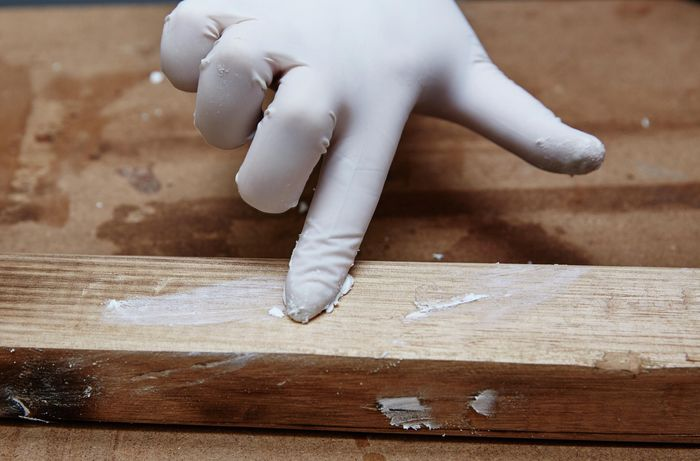 Person wearing a glove and applying spakfilla to holes in timber.