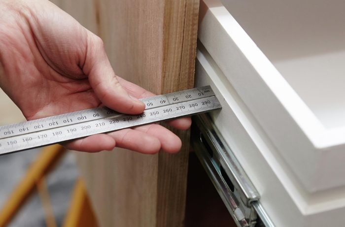 A person using a metal ruler to measure between a drawer and a timber panel