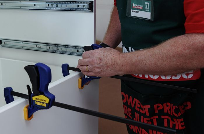 Person clamping cabinet panel