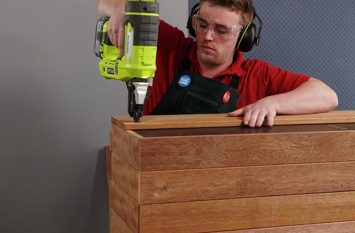 A person attaching decking timber to the top of a bench seat