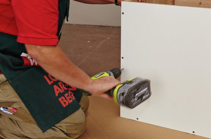 A person assembling a cabinet using a cordless driver