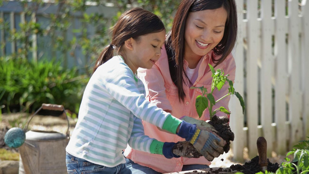 Mother and daughter planting in the garden