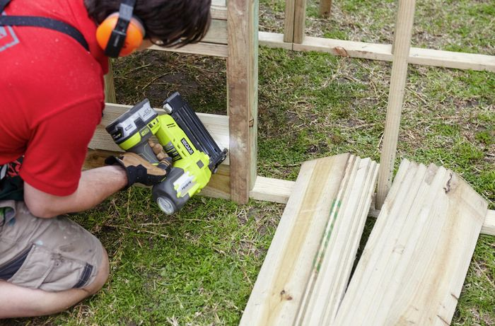 Panels of timber being nailed to a wooden wall frame for a chicken coop