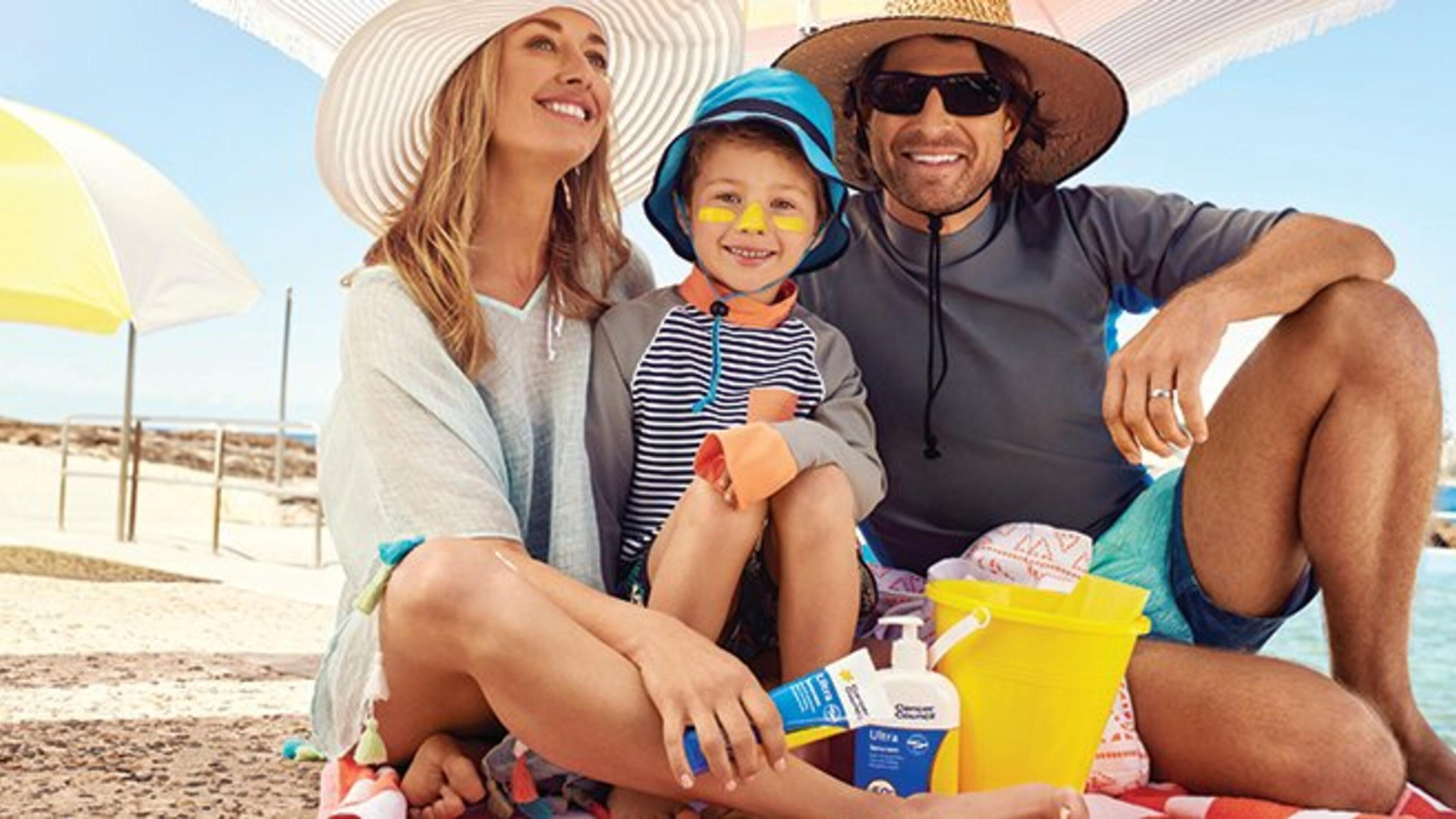 Woman, man and child at the beach wearing sunscreen and hats