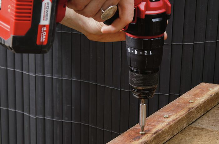 A wooden benchtop being fixed together with screws and a power drill
