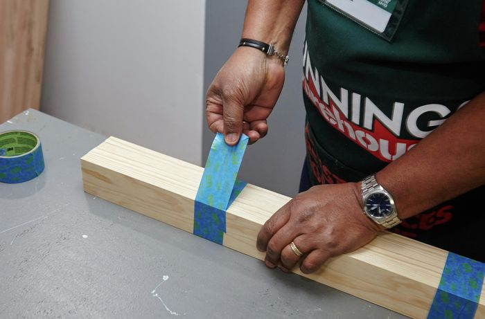 A person taping lengths of pine timber together