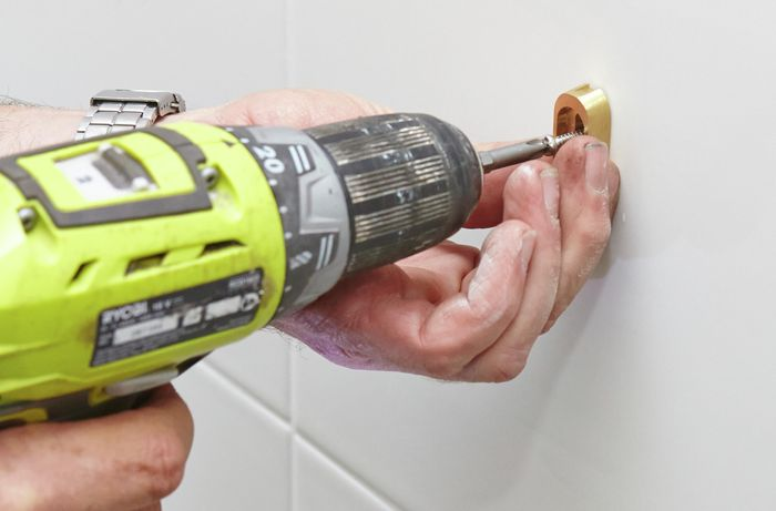 A person attaching towel rail fittings to a tile wall using a cordless drill