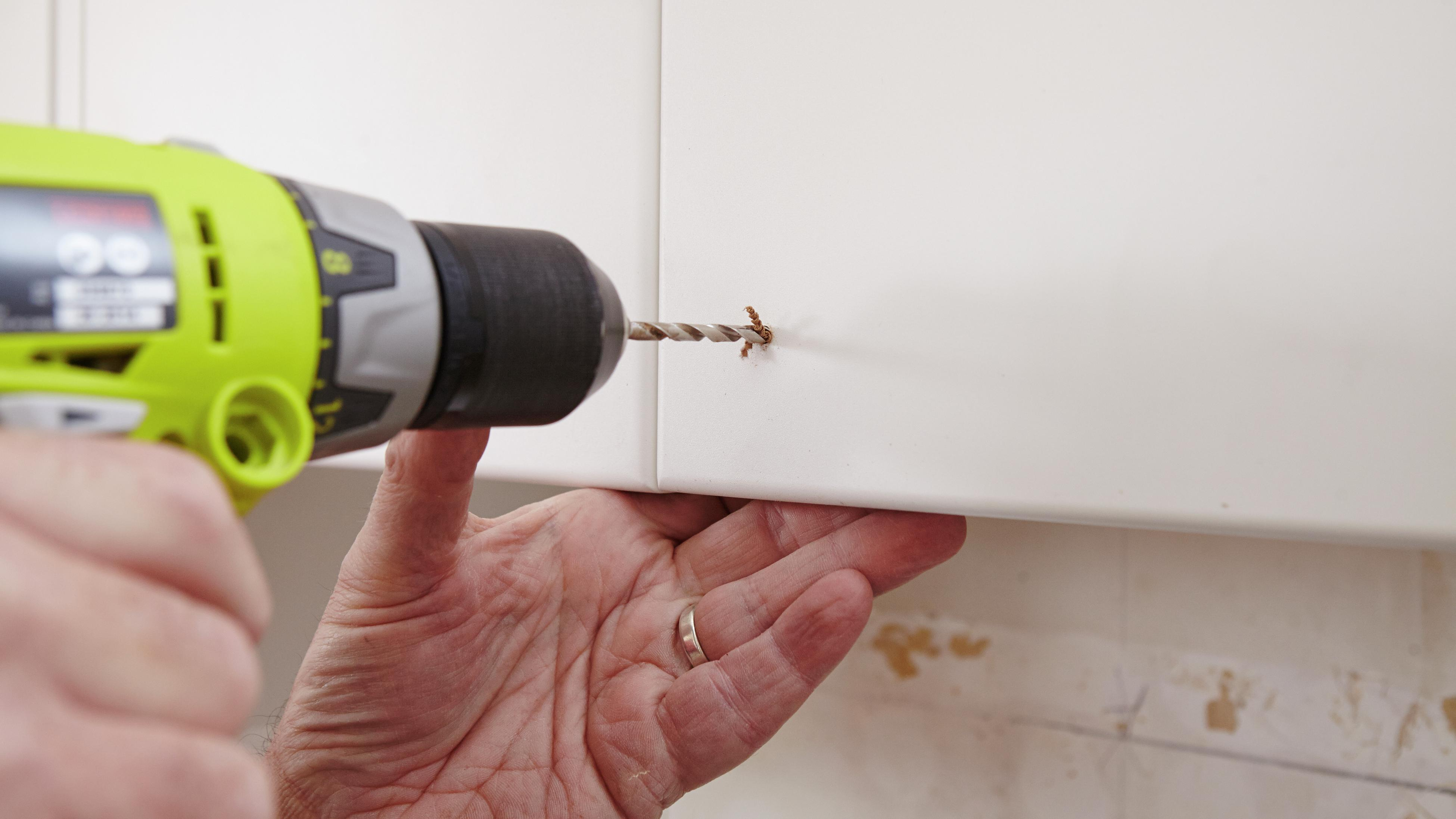 Person drilling into a kitchen cabinet.