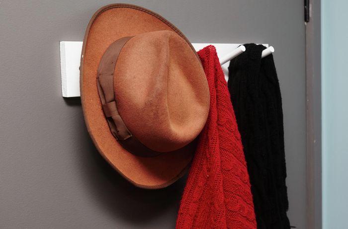 Coat rack on door with hat and coats