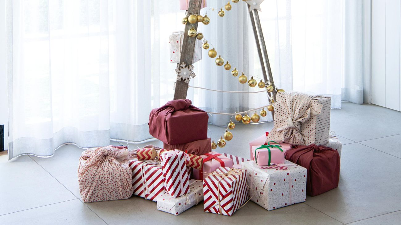 Timber ladder covered with tinsel, surrounded by gifts.