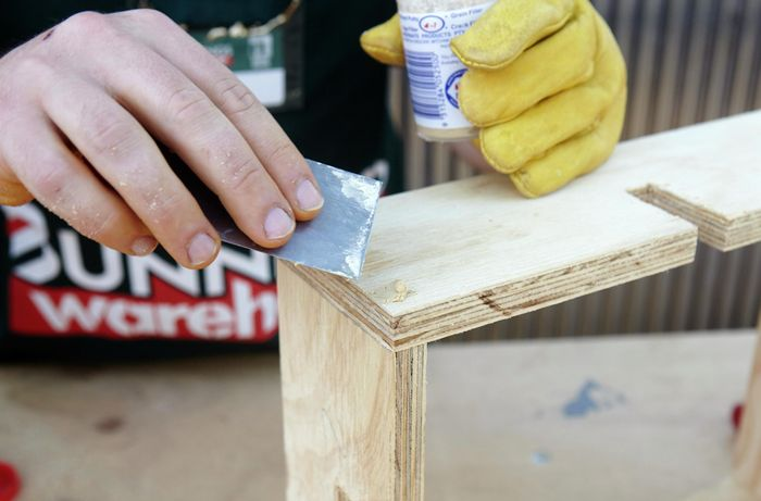 Person filling holes in timber with putty