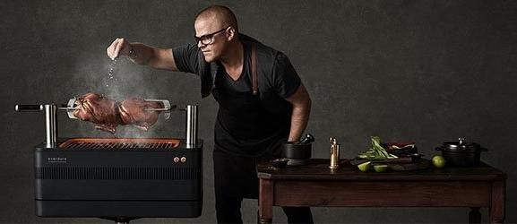 Heston Blumenthal putting salt on food cooking on BBQ.