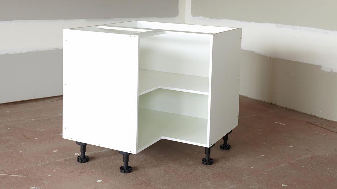 A corner cabinet on adjustable legs