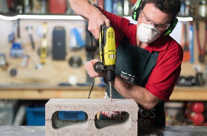 Team member using hammer drill on a brick
