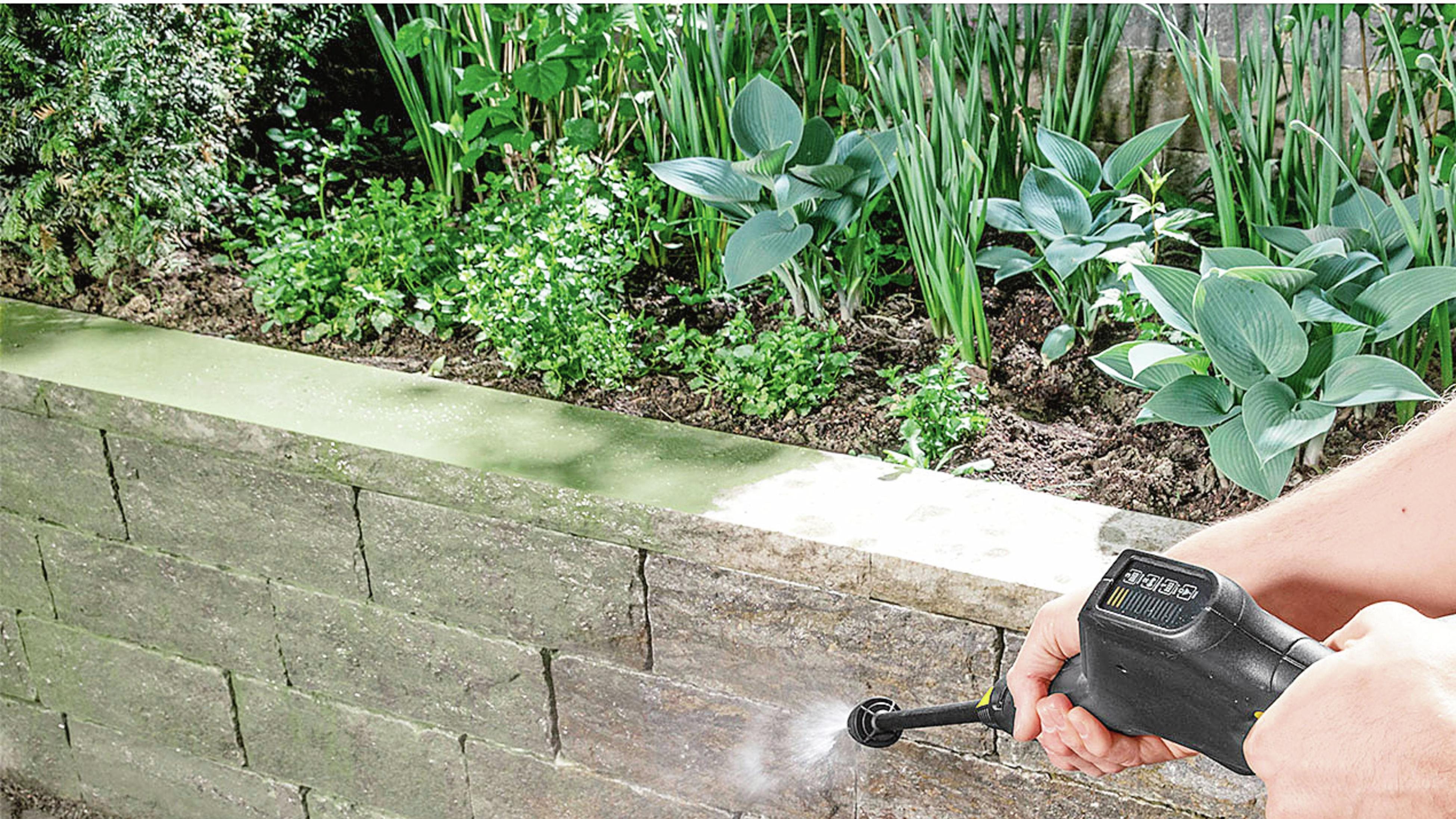A pressure washer cleans a grey brick fence.