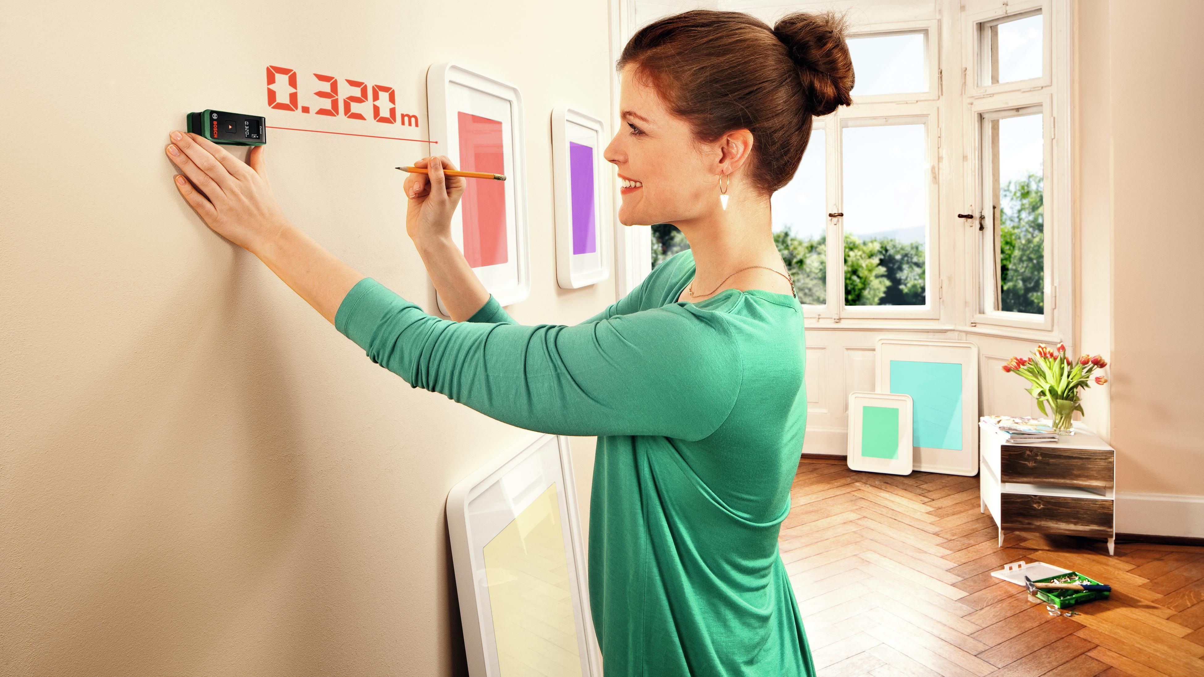 Person using digital measuring tool on wall.
