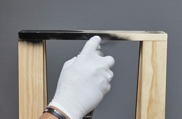 A person spray painting timber black