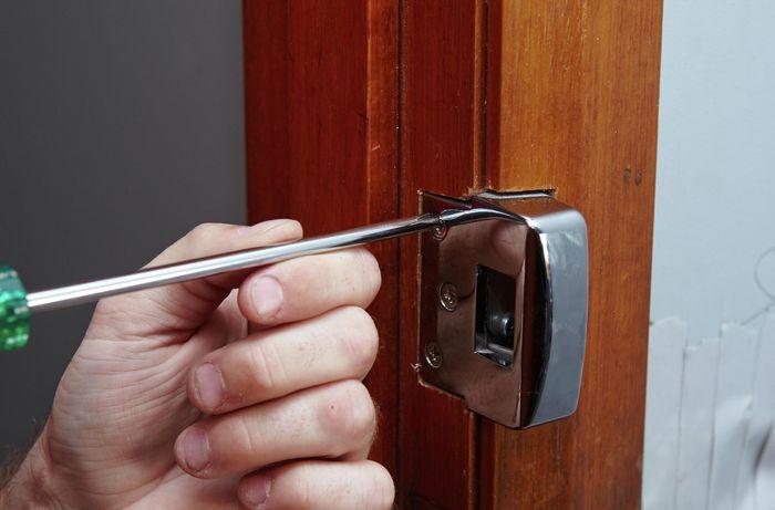 A door latch being unscrewed from a door jamb