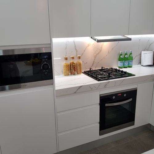 Kitchen with white benchtops and cabinets with microwave, oven and gas cooktop