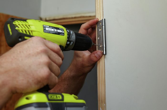 Holes being drilled into a door frame for screws, using a door hinge as a guide